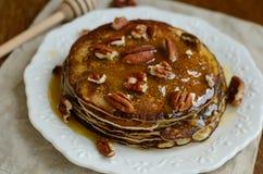 自创稀薄的薄煎饼用蜂蜜和山核桃果在白色porcel 免版税库存图片