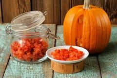 自创糖煮的南瓜在玻璃瓶子和白色板材机智片 免版税库存照片