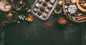 自创素食主义者块菌状巧克力果仁糖用干果子和胡说的混合成份在黑暗的背景,顶视图,边界 免版税库存图片