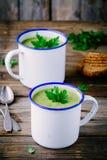 自创绿色夏南瓜奶油汤用在杯子的荷兰芹 库存图片