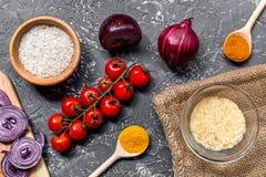 自创肉菜饭成份构成用米,蕃茄,在黑暗的桌背景顶视图的葱 图库摄影