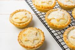自创肉馅饼 与苹果填装在金属冷却的机架的葡萄干坚果的传统英国圣诞节酥皮点心点心 库存照片