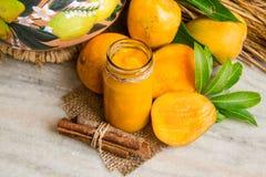 自创芒果果酱用新鲜水果和切片芒果,在一块白色大理石的肉桂条 库存图片