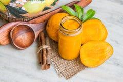 自创芒果果酱用新鲜水果和切片芒果,在一块白色大理石的肉桂条 免版税库存照片