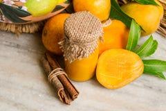 自创芒果果酱用新鲜水果和切片芒果,在一块白色大理石的肉桂条 免版税图库摄影