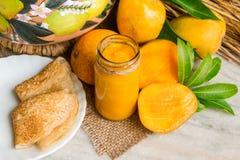 自创芒果果酱用新鲜水果和切片芒果,在一块白色大理石的薄煎饼 免版税库存图片
