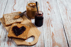 自创花生酱和果冻三明治在木背景 免版税图库摄影