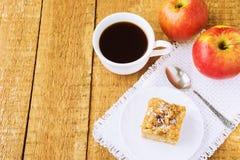 自创苹果饼和咖啡在木桌上 免版税库存图片