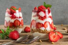 自创草莓酸奶冷甜点用在玻璃的格兰诺拉麦片,薄荷和新鲜的莓果在土气木桌上 库存照片