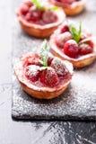 自创草莓馅饼用在板岩板材,黑背景的搽粉的糖 关闭 免版税库存照片