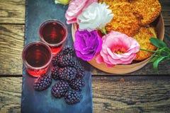 自创莓果利口酒、莓果、花和饼干 免版税图库摄影