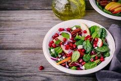 自创菠菜、苹果、胡桃、红洋葱沙拉用山羊乳干酪和石榴 库存照片