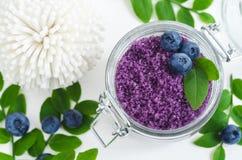 自创蓝莓糖在一个玻璃瓶子洗刷/腌制槽用食盐/脚浸泡 自然护肤的DIY化妆用品 复制空间 免版税库存照片