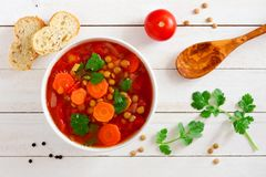 自创蕃茄,扁豆汤,上面在白色木头 免版税库存图片