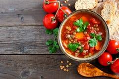 自创蕃茄,扁豆汤,在看法在木头的角落边界上 免版税库存照片