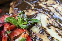 自创薄煎饼与,水多的草莓、新鲜薄荷和巧克力 库存图片