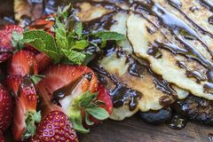 自创薄煎饼与,水多的草莓、新鲜薄荷和巧克力 库存照片