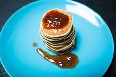 自创薄煎饼用在一块蓝色板材的果酱 免版税库存照片