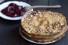 自创薄煎饼用在一张黑暗的木桌上的山莓果酱 忏悔节 免版税库存照片