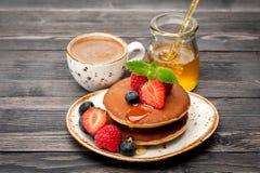 自创薄煎饼用蜂蜜、浓咖啡和莓果 免版税库存图片