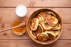 自创薄煎饼用蜂蜜和杯在木盘的牛奶 免版税库存图片