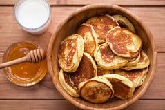 自创薄煎饼用蜂蜜和杯在木盘的牛奶 库存照片
