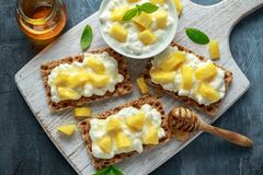 自创薄脆饼干多士用酸奶干酪、菠萝和蜂蜜在白色木板 免版税库存照片