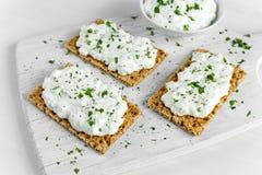 自创薄脆饼干多士用酸奶干酪和荷兰芹在白色木板 免版税库存图片