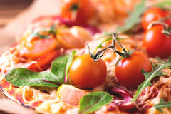 自创薄饼用烟肉、蕃茄、菠菜、芝麻菜和乳酪 图库摄影
