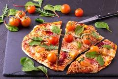 自创薄饼用烟肉、蕃茄、菠菜、芝麻菜和乳酪 免版税库存图片