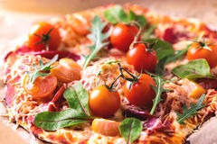 自创薄饼用烟肉、蕃茄、菠菜、芝麻菜和乳酪 库存图片