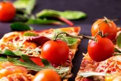 自创薄饼用烟肉、蕃茄、菠菜、芝麻菜和乳酪 库存照片