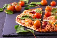 自创薄饼用烟肉、蕃茄、菠菜、芝麻菜和乳酪 免版税库存照片
