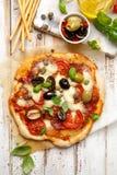 自创薄饼用蕃茄、橄榄、蒜味咸腊肠、无盐干酪乳酪和新鲜的蓬蒿在一张木土气桌上 图库摄影