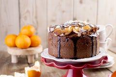 自创蛋糕用蜜桔和杏仁,用巧克力 在一块白色板材上,茶的早餐杯子的 木背景,空间 库存照片