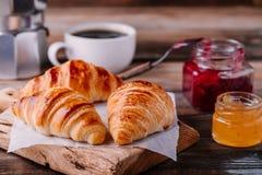 自创被烘烤的新月形面包用果酱和咖啡在木土气背景 库存图片