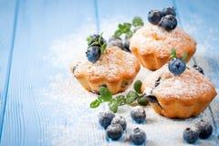 自创被烘烤的松饼用蓝莓,新鲜的莓果,薄菏,搽粉了在蓝色木背景的糖 顶视图 库存照片