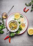 自创调味汁或色拉调味品在碗有成份的:新鲜的草本、油、柠檬和蜂蜜在灰色具体背景,上面竞争 免版税库存图片