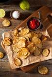 自创辣石灰和胡椒被烘烤的土豆片 免版税库存照片