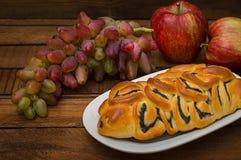 自创酥皮点心、甜鸦片饼在背景新鲜水果,苹果和葡萄静物画  库存照片