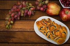 自创酥皮点心、甜鸦片饼在背景新鲜水果,苹果和葡萄静物画  免版税库存图片