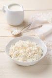 自创酸奶干酪和水罐在一张白色木桌上的奶油 免版税库存图片