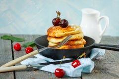 自创酸奶干酪薄煎饼用在铸铁煎锅的樱桃 免版税库存图片