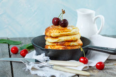 自创酸奶干酪薄煎饼用在铸铁煎锅的樱桃 免版税库存照片