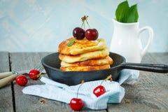 自创酸奶干酪薄煎饼用在铸铁煎锅的樱桃 库存图片