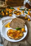 自创酸面团三明治用金桔果酱和黄油在一块白色板材 免版税库存照片