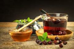 自创野玫瑰果茶 传统治疗寒冷和流感 在一张木桌上的干莓果 热的野玫瑰果茶 冬天茶 库存图片