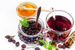 自创野玫瑰果茶 传统治疗寒冷和流感 干灌木干莓果在白色背景的 热的野玫瑰果茶 胜利 库存图片