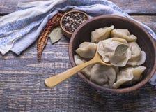 自创饺子煮沸他们的面团和肉末在一个木板,背景 库存图片
