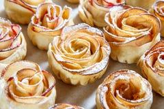 自创饼干用苹果以的形式在烘烤纸上升了 免版税图库摄影